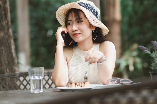 De vrouw die van azië smartphone in vrije tijd gebruiken
