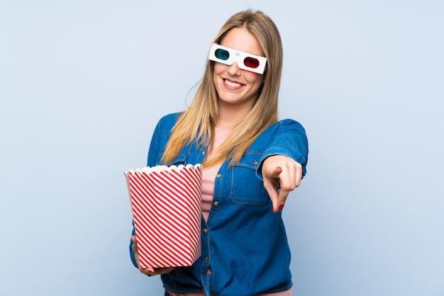 De vrouw die van de blonde de vinger van popcornspunten eet bij u