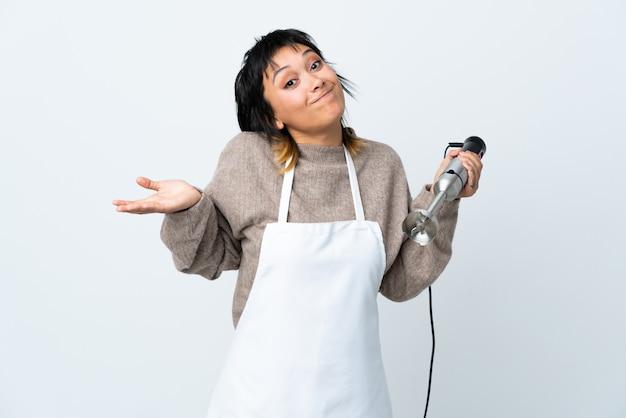 De vrouw die van de chef-kok handmixer over geïsoleerde witte ruimte gebruikt die twijfels heeft met verwarren gezichtsuitdrukking