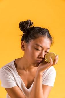 De vrouw die van de close-up de helft van citroen houdt