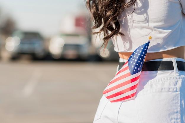 De vrouw die van de close-up de vlag van de vs in achterzak houdt