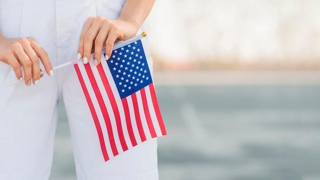 De vrouw die van de close-up de vlag van de vs in handen houdt