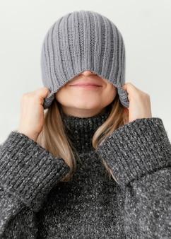 De vrouw die van de close-up hoed naar beneden trekt