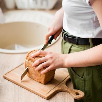 De vrouw die van de close-up organisch brood snijdt