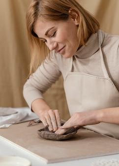 De vrouw die van de close-upsmiley aardewerk doet