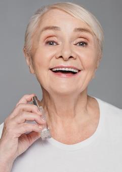 De vrouw die van de close-upsmiley parfum gebruikt