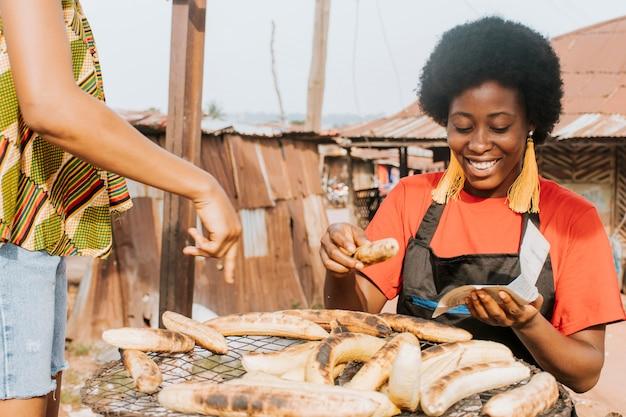De vrouw die van de close-upsmiley voedsel maakt