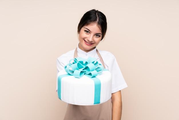 De vrouw die van de gebakjechef-kok een grote cake over geïsoleerde muur met gelukkige uitdrukking houdt