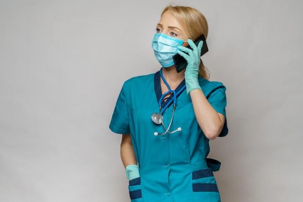 De vrouw die van de medische artsenverpleegster beschermend masker en latexhandschoenen dragen - die op de telefoon spreken