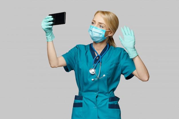 De vrouw die van de medische artsenverpleegster beschermend masker en latexhandschoenen dragen - videotelefonerend op de telefoon
