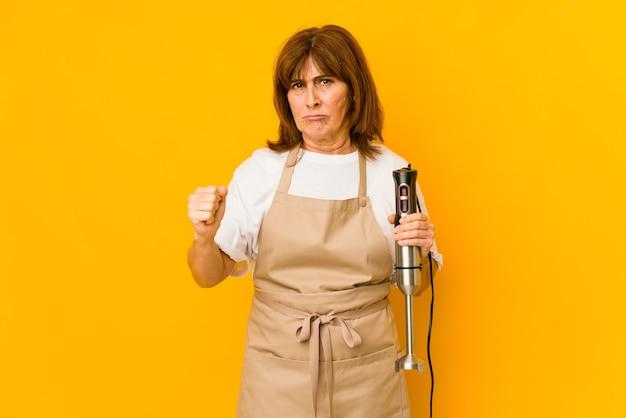 De vrouw die van de middelbare leeftijd de kaukasische kok een geïsoleerde mixer houdt die vuist toont aan camera, agressieve gezichtsuitdrukking.