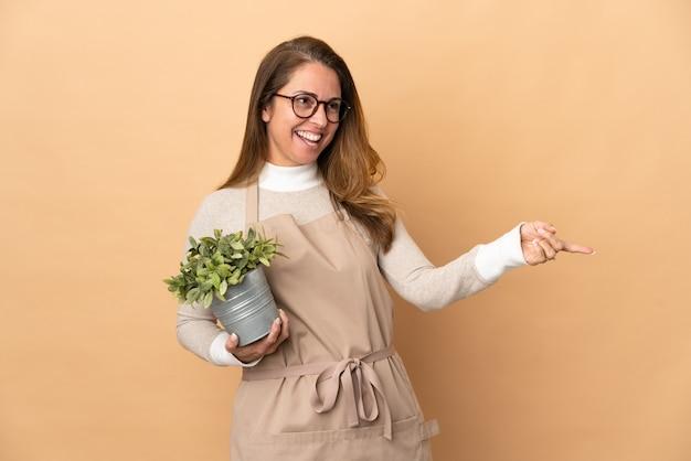 De vrouw die van de middelbare leeftijdstuinman een geïsoleerde plant houdt