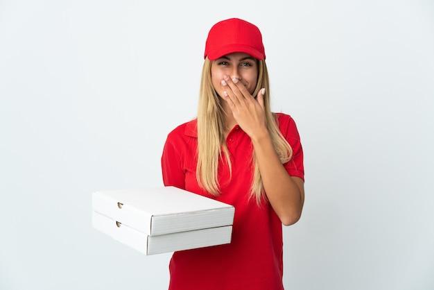De vrouw die van de pizzabezorger een pizza houdt die op witte muur wordt geïsoleerd gelukkig en het glimlachen behandelende mond met hand