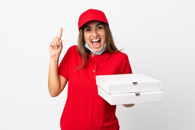 De vrouw die van de pizzakoerier een pizza houdt en tegen het coronavirus beschermt met een masker over geïsoleerde witte muur die een groot idee benadrukt
