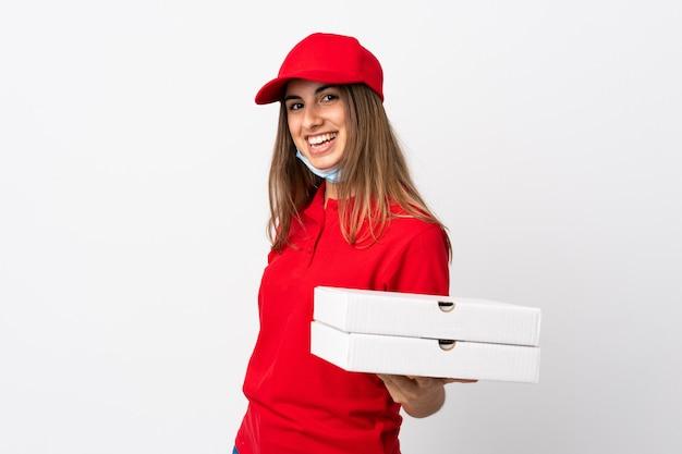 De vrouw die van de pizzakoerier een pizza houdt en tegen het coronavirus beschermt met een masker over geïsoleerde witte muur die veel glimlacht