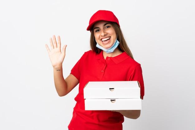 De vrouw die van de pizzakoerier een pizza houdt en tegen het coronavirus met een masker beschermt over geïsoleerde witte muur die met hand met gelukkige uitdrukking groeten