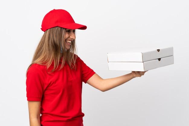 De vrouw die van de pizzakoerier een pizza houdt en tegen het coronavirus met een masker over geïsoleerde witte muur met gelukkige uitdrukking beschermt