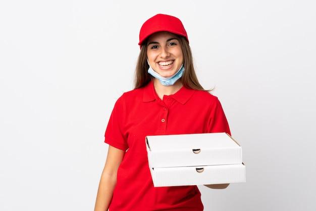 De vrouw die van de pizzakoerier een pizza over witte muur houden die veel glimlachen