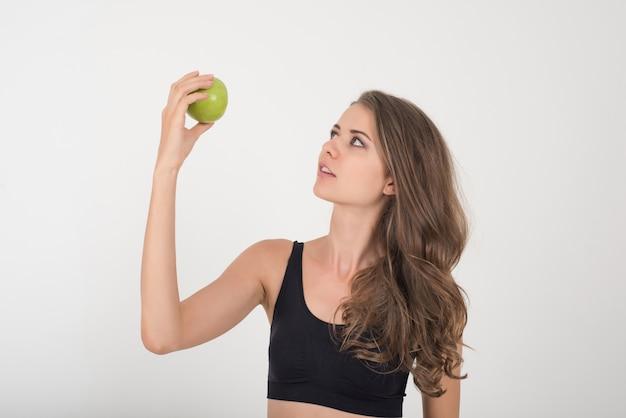 De vrouw die van de schoonheid groene appel houdt terwijl geïsoleerd op wit