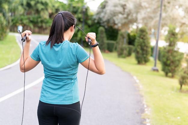 De vrouw die van de sportenbeginner oefeningen met touwtjespringen doen