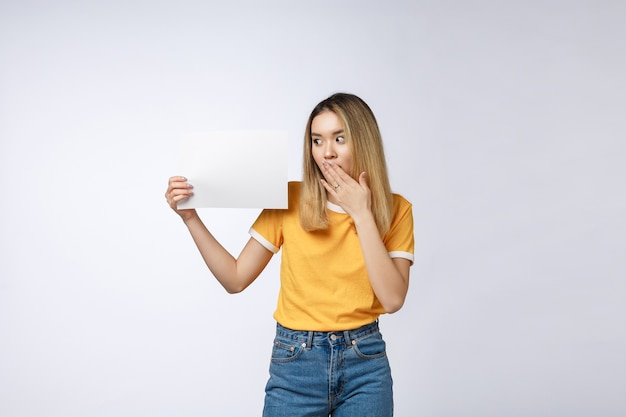 De vrouw die van het bannerteken over rand van leeg leeg document aanplakbord gluren