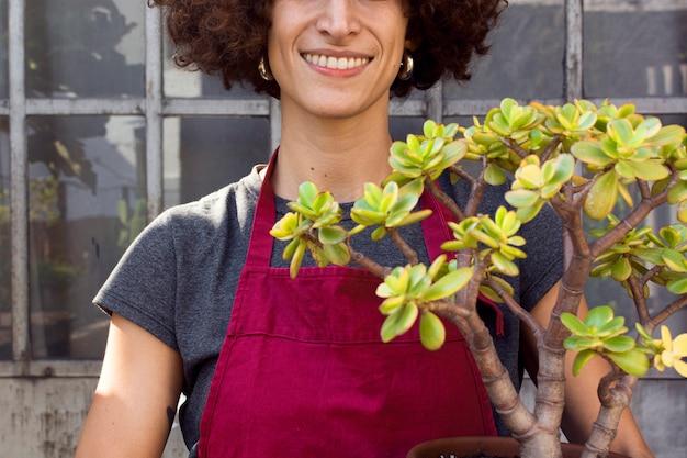 De vrouw die van smiley thuis het tuinieren doet