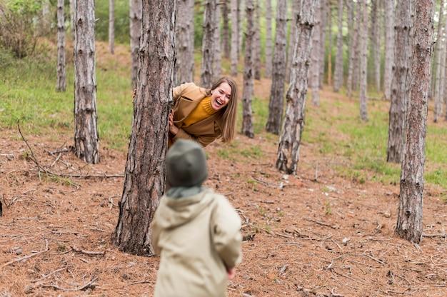 De vrouw die van smiley zich achter een boom van haar zoon verbergt