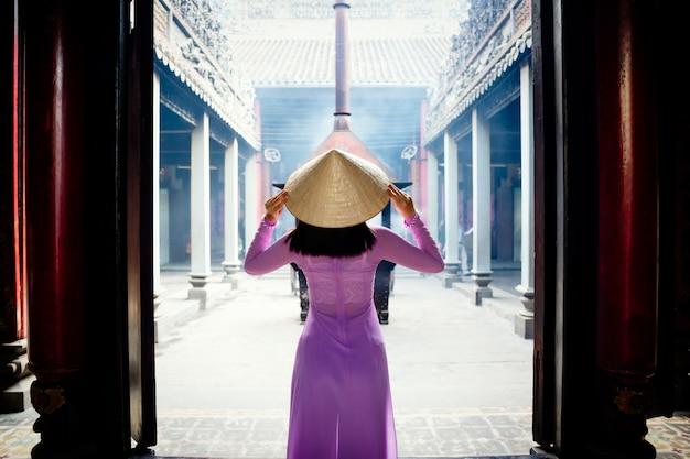 De vrouw die van vietnam ao dai-cultuur traditioneel bij oude tempel in ho chi minh in vietnam dragen