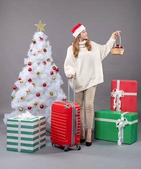 De vrouw die van vooraanzicht blonde kerstmis met santahoed mand met kerstmisspeelgoed bekijkt