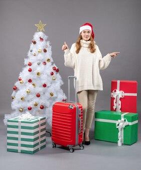 De vrouw die van vooraanzichtkerstmis met santahoed duim maakt ondertekent omhoog dichtbij witte kerstmisboom met rood kerstmisspeelgoed