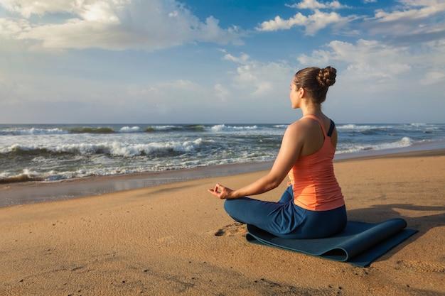 De vrouw die yoga lotus doet stelt oudoors bij strand