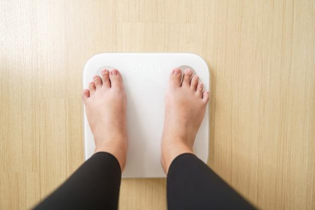 De vrouw die zich op weegt, weegt elektronische weegschalen. dieet levensstijl concept om buik te verminderen