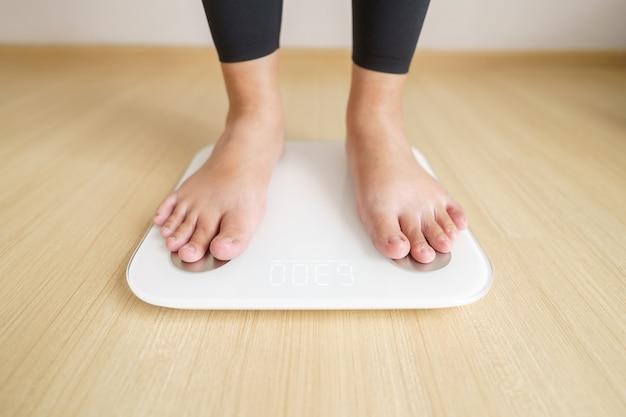 De vrouw die zich op weegt, weegt elektronische weegschalen. dieet levensstijl concept om te verminderen