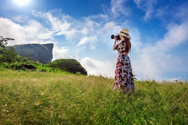 De vrouw die zich op weide bevindt en camera vasthoudt, neemt foto bij de bergen van phu chi fa in chiangrai, thailand. reis concept.