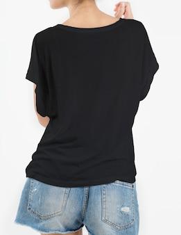 De vrouw die zwarte t-shirt draagt en scheurt jeans op wit kort