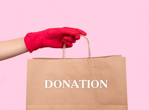 De vrouw dient een rubberen handschoen in met papieren zak met tekstdonatie