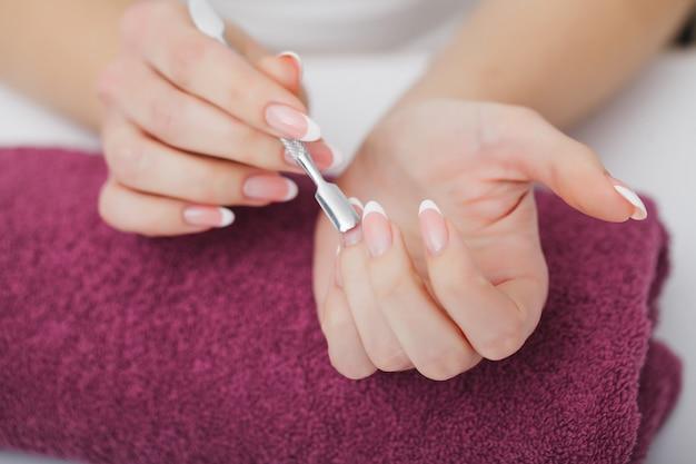 De vrouw dient een spijkersalon in die een manicureprocedure ontvangen