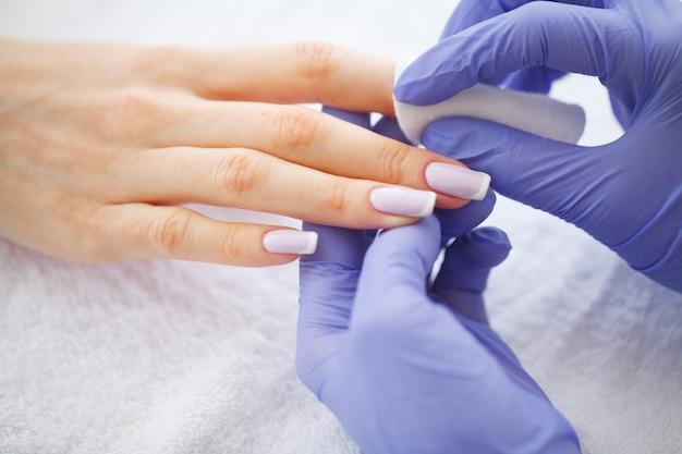 De vrouw dient een spijkersalon in die een manicureprocedure ontvangen.