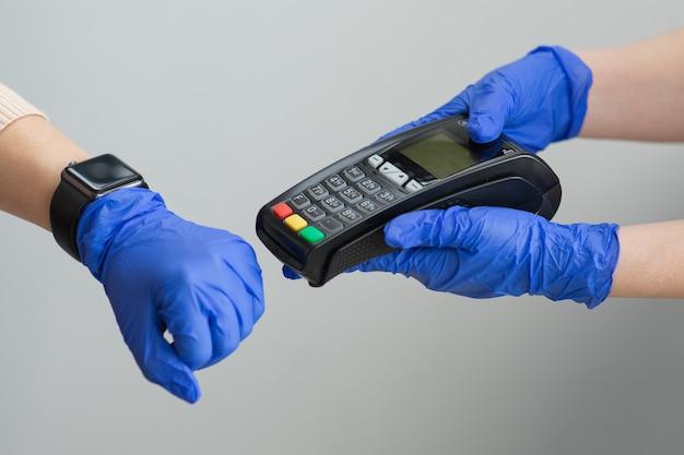 De vrouw dient handschoenen in gebruikend smartwatch om product bij de verkooppuntterminal in een detailhandel te kopen met het gebruik van nfc identificatiebetalingstechnologie voor verificatie.
