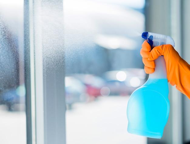De vrouw dient oranje rubberhandschoenen in schoonmakend venster met reinigingsmachine nevel