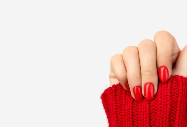 De vrouw dient sweater met rode manicure op grijs in