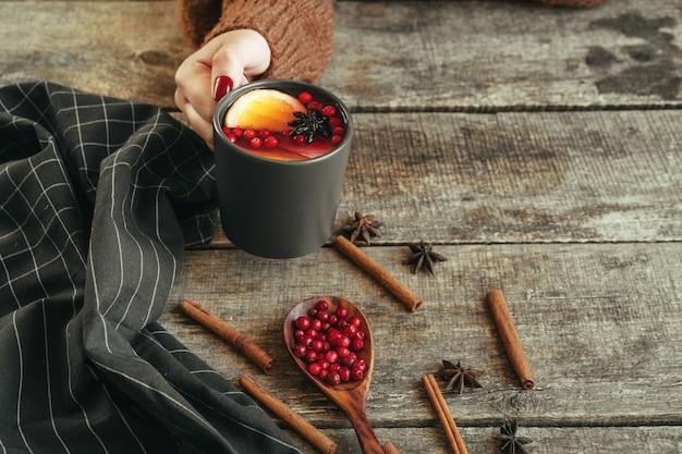 De vrouw dient warme sweater in houdend een kop glühwein