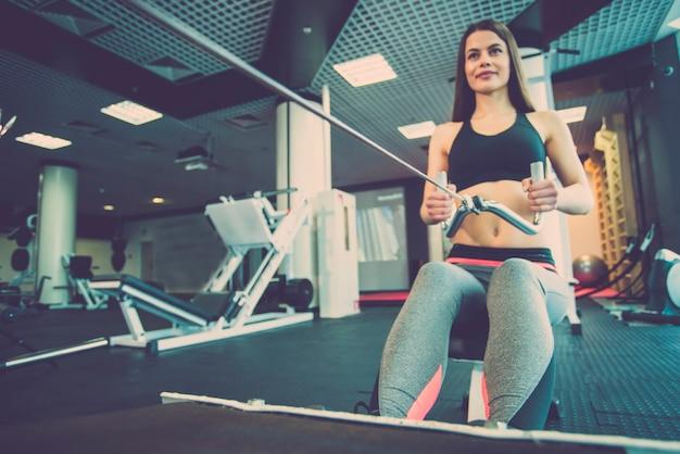 De vrouw doet oefeningen op de apparatuur van het fitnesscentrum