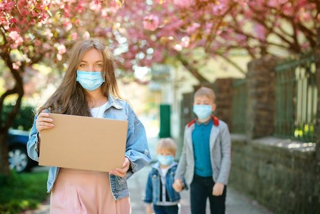 De vrouw draagt in openlucht gezichtsmasker. wijfje dat lege raad houdt tijdens quarantaine. familie dragen veiligheidsmaskers lopen op straat.