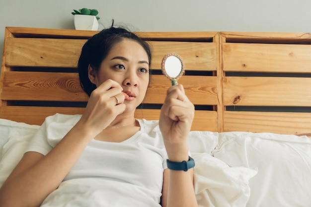 De vrouw draagt make-up op haar bed in de slaapkamer.
