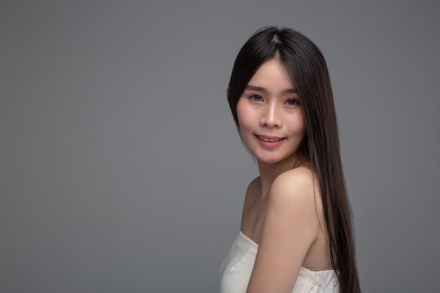 De vrouw draagt witte strapless tops en gezicht naar links.