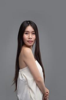 De vrouw draagt witte strapless tops en gezicht naar rechts.