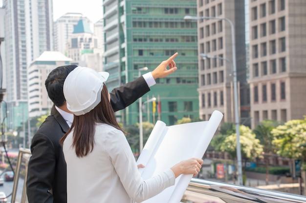 De vrouw draagt witte veiligheidshoed en de tablet en de zakenman bekijken de bouw