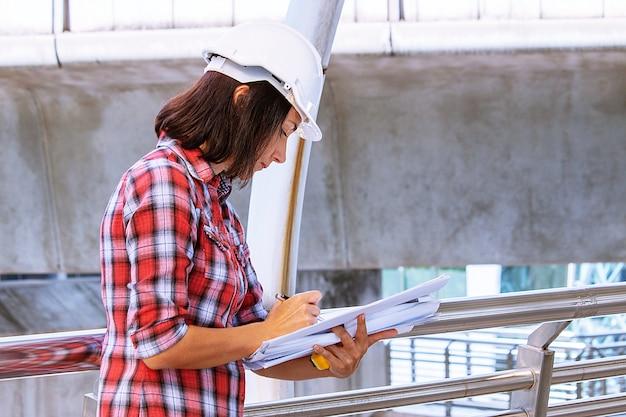 De vrouw draagt witte veiligheidshoed werkt bij bouwwerf