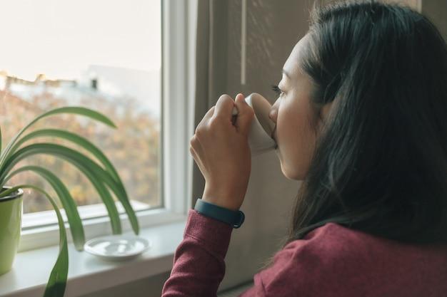 De vrouw drinkt koffie bij de ramen om het uitzicht op de stad te bewonderen.